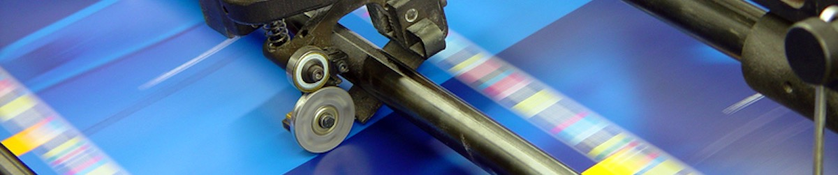 an image of an offset printer showing roller and multiple colors passing
